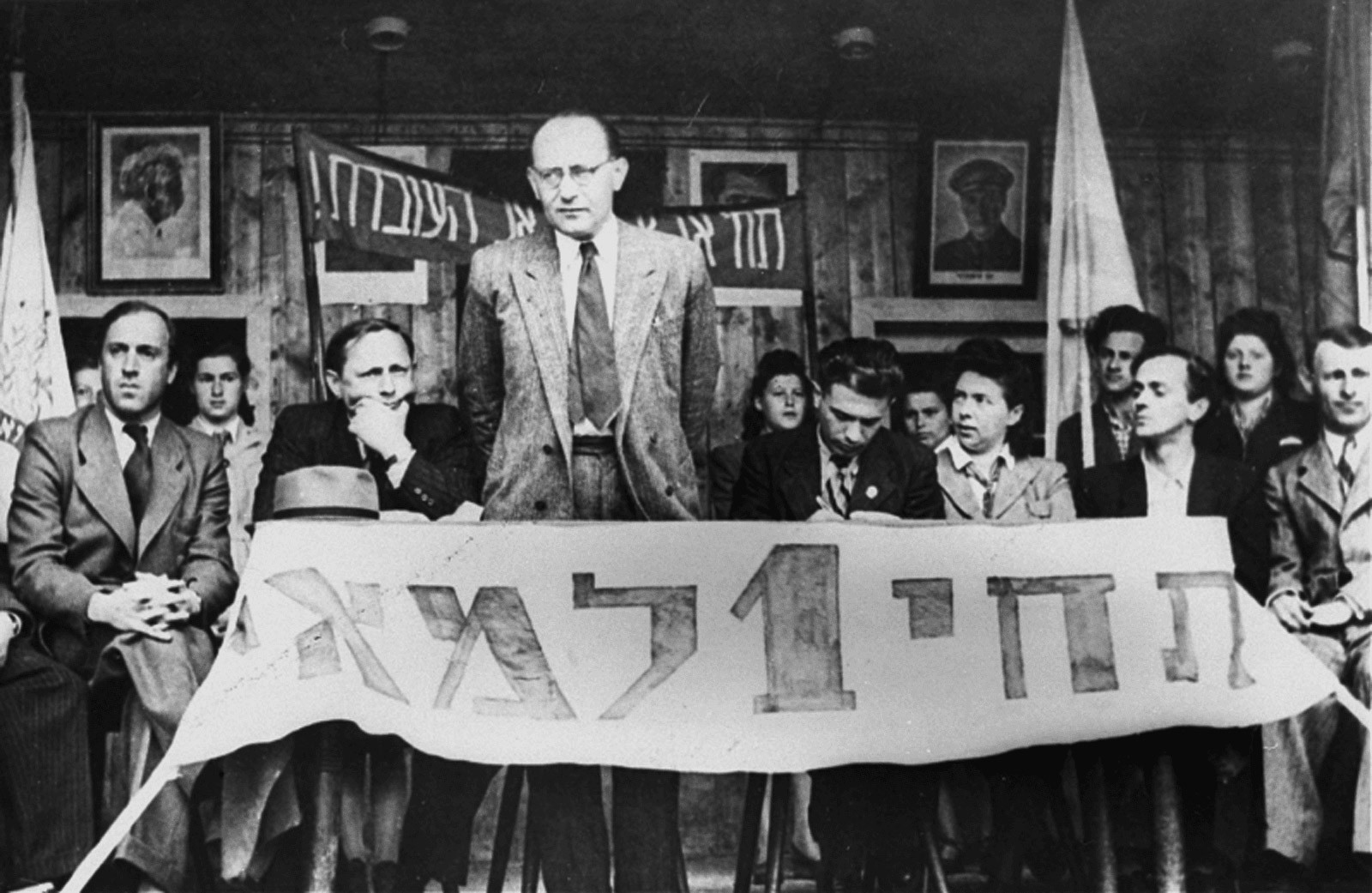 """May 1st, holiday of the working class: Chaim Yahil as emissary of the Jewish Agency with survivors of Nazi persecution (""""Displaced Persons"""") in the DP Camp of München-Neu-Freimann (1946 / 1948).  The Jewish Agency organized Jewish immigration to Palestine.  Photo: Jack Sutin / United States Holocaust Memorial Museum, courtesy of Saul Sorrin. der NS-Verfolgung (""""Displaced Persons"""") im DP-Camp München-Neu-Freimann (1946 / 1948). Die Jewish Agency organisierte die Einwanderung nach Palästina.  Foto: Jack Sutin / United States Holocaust Memorial Museum, courtesy of Saul Sorrin"""